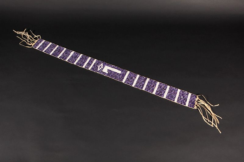 This wampum belt has several motifs made with white beads contrasted with purple ones. The central motif is an axe.